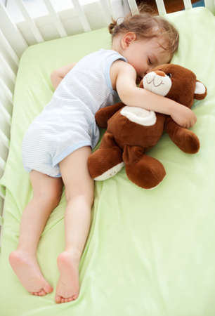 child in bed: Sweet child sleeping with teddy bear