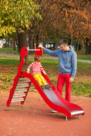 children s: Father and son having fun at the slide