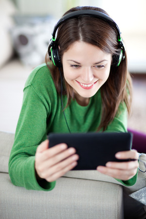Image of young woman relaxing and using digital tablet photo