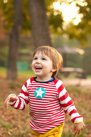 ��beautiful boy�: Image of beautiful boy running and smiling, shallow depth of field