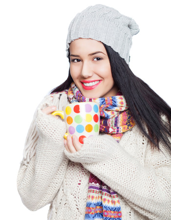 Image of beautiful young woman having a cup of hot drink, isolated on white photo
