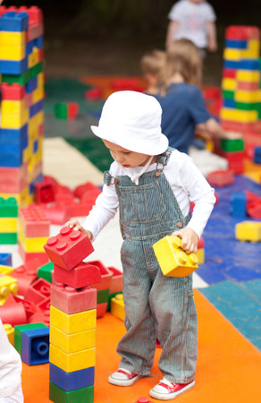 Cute two year old boy playing with toy blocks photo