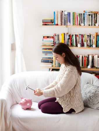 thrift box: Young woman breaking the piggy bank Stock Photo