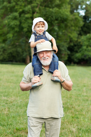 shoulder ride: Grandfather and grandson having fun outdoors
