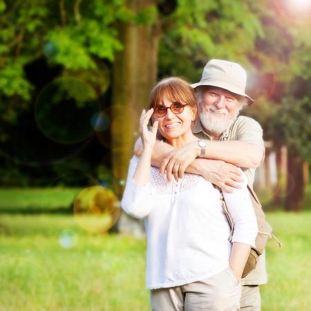 personas abrazadas: Cerca de la pareja de ancianos que tienen buen tiempo al aire libre, poca profundidad de campo