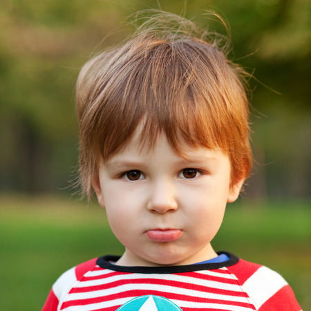 sulking: Close up portrait of beautiful boy pouting, shallow depth of field Stock Photo