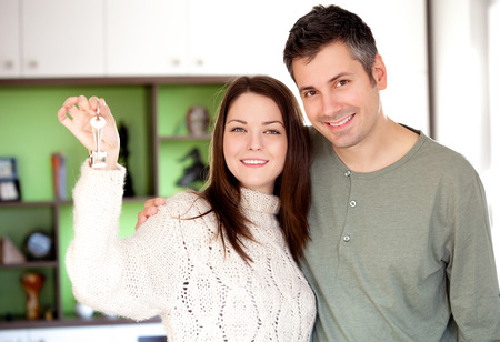 key ring: Image of happy young couple smiling and holding key ring Stock Photo
