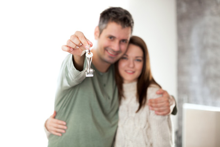 key ring: happy young couple smiling and holding key ring, shallow depth of field focus on foreground Stock Photo