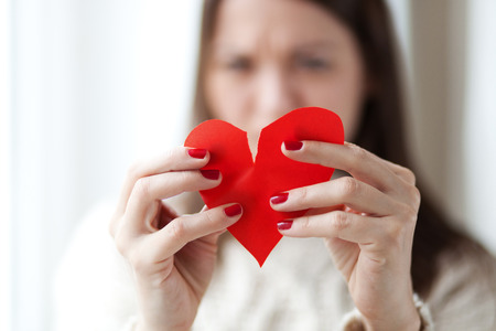 breaking up: woman tearing paper heart apart, shallow depth of field Stock Photo