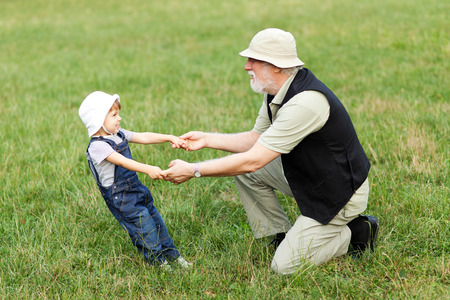 grandchildren: Grandchild and grandfather holding hands and having fun outdoor