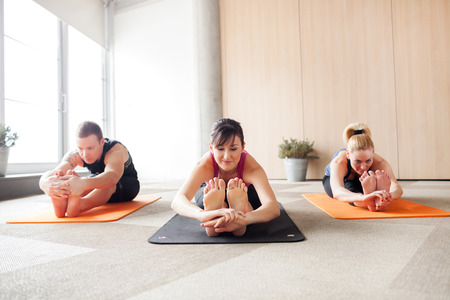 barefeet: Three people in a yoga class holding a pose Stock Photo