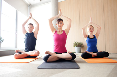 female pose: Young people meditating in a yoga class