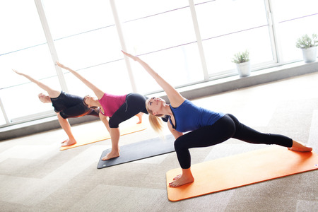 woman pose: Young people holding triangle pose in a yoga class Stock Photo