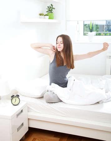 despertarse: Mujer joven que despierta feliz, después de una buena noche de sueño Foto de archivo