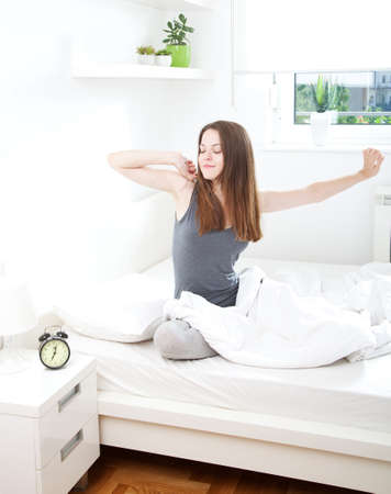 arms up: Young woman waking up happily, after a good night sleep Stock Photo