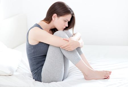 periods: Sad looking young woman sitting on bed, on white background Stock Photo