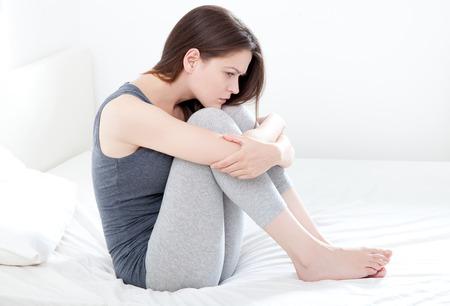 ragazza malata: Triste cerca giovane donna seduta sul letto, su sfondo bianco