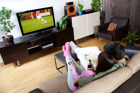 sofa television: Young couple relaxing, watching TV and having a beer Stock Photo