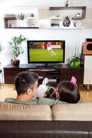 pareja viendo television: Pareja joven relajarse, ver la televisión y tomar una cerveza