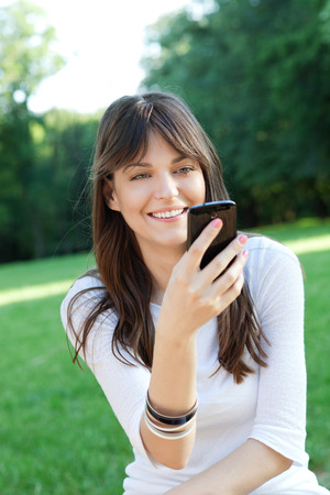 Young beautiful woman using cell phone outdoor photo