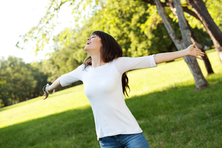 outstretching: Beautiful young woman outstretching arms and smiling, shallow depth of field Stock Photo