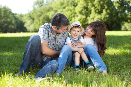 family tickle: Portrait of beautiful family having fun on a meadow