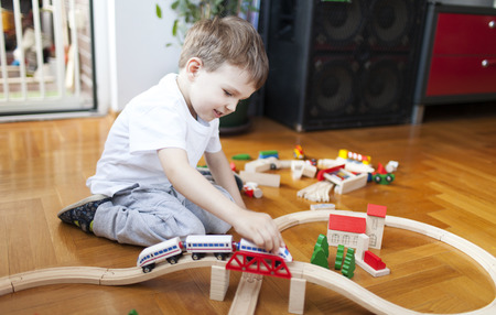 wood railroad: Little boy playing with wooden train set Stock Photo