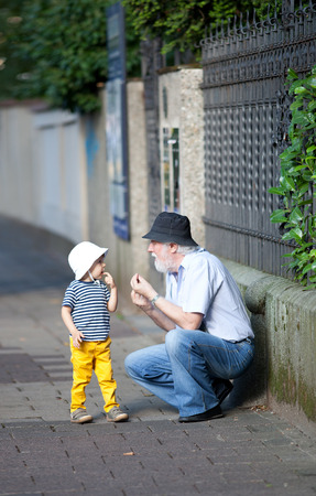 to crouch: Grandfather explaining something to a boy at the sidewalk