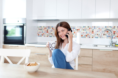 calling on phone: Young beautiful woman using cell phone and having a coffee in the kitchen