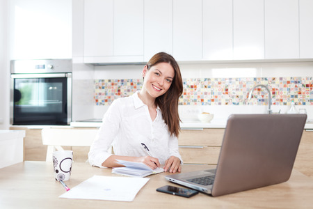 working at home: Beautiful young woman working on laptop at home Stock Photo