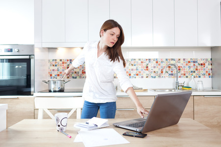 home cooking: Beautiful young woman working on laptop and cooking at the same time Stock Photo