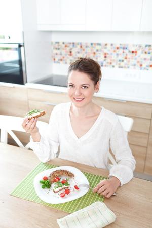 comiendo pan: Mujer joven hermosa que tiene un desayuno saludable