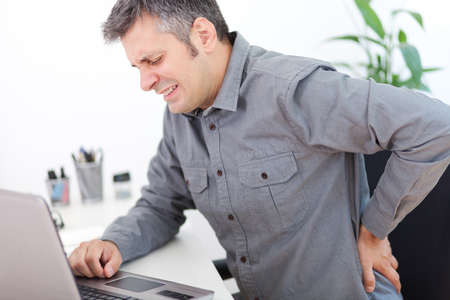ache: Image of a young man having a back pain while sitting at the working desk