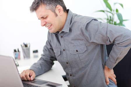 chory: Obraz młodego człowieka o ból pleców podczas siedzenia przy biurku pracy