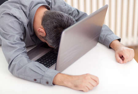 drowse: Image of a man sleeping at the working desk Stock Photo