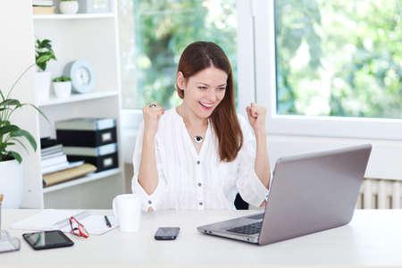 Obraz extatické mladé ženy sedí u stolu Reklamní fotografie