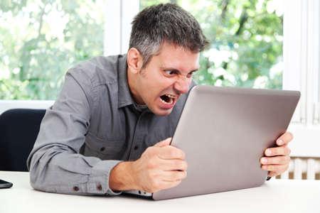 desesperado: Imagen del hombre en la formación de crema escritorio y gritando en la computadora portátil
