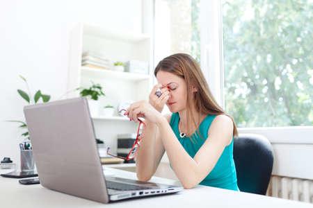 agotado: Imagen de una mujer en el mostrador de la oficina, tener dolor de cabeza