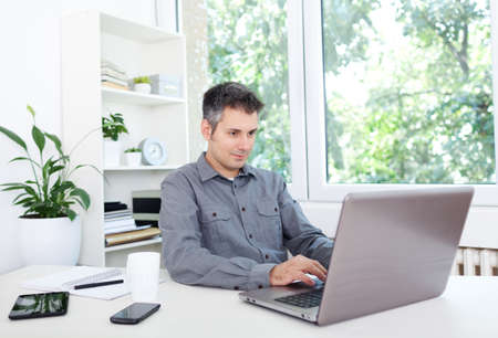 man working computer: Image of a confident young man sitting at working desk