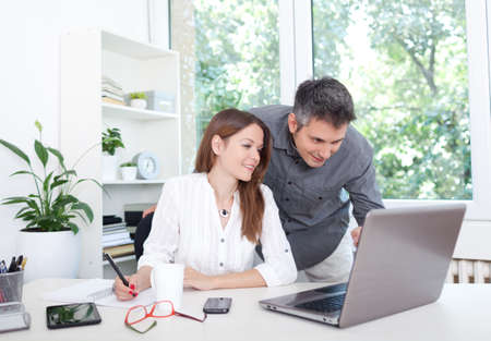 wireless woman work working: Beautiful young couple in office, using laptop Stock Photo
