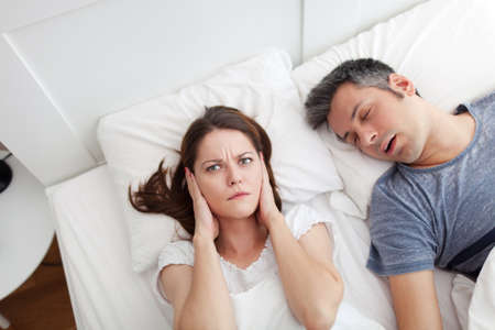 tired man: Woman covering ears, annoyed by the snoring of her husband