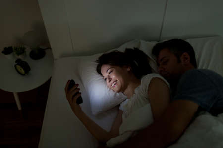 lady on phone: Young woman using mobile phone, while husband asleep