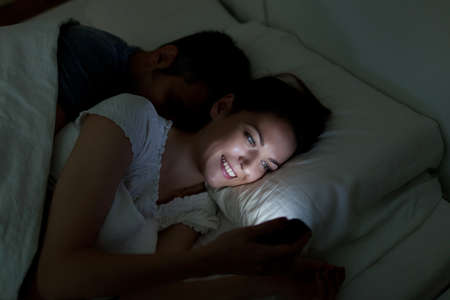 wives: Young woman using mobile phone, while husband asleep