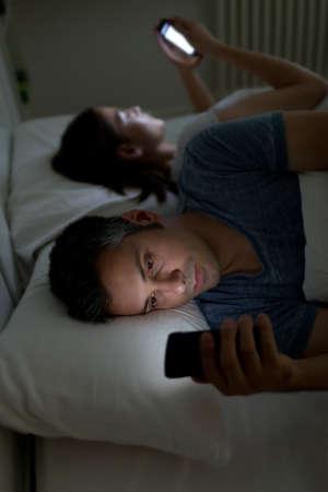 enamorados en la cama: Pareja joven con teléfonos inteligentes en su cama
