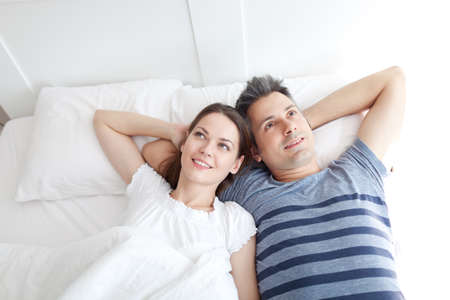 bed: Young couple lying on bed, relaxing Stock Photo