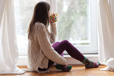 invierno: Hermosa mujer joven sentada junto a la ventana con bebida caliente