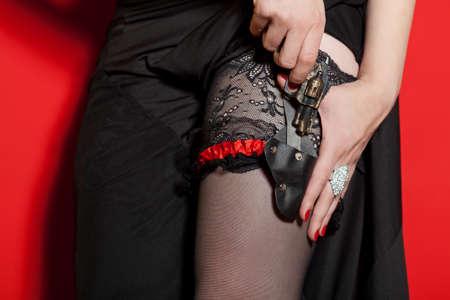 mujer con arma: Mujer sacar peque�a pistola de la funda Foto de archivo