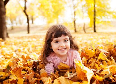 niñas jugando: Imagen de la hermosa chica en la pila de hojas de otoño, la profundidad de campo