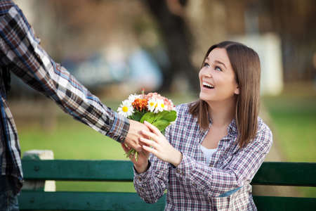 Happy valentines day: Young woman receiving a bunch of wild flowers on a date