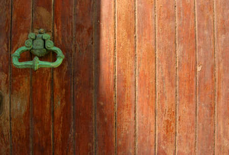 residencial: Old brass knocker covered with green patina on wooden door.